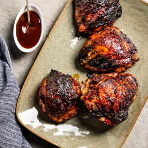BBQ Chicken Thighs with sauce on platter