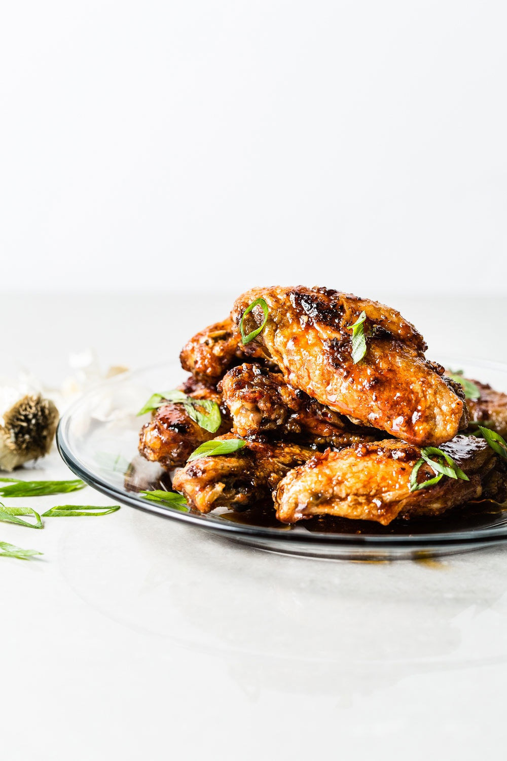Honey-Garlic Air Fried Chicken Wings stacked on glass plate