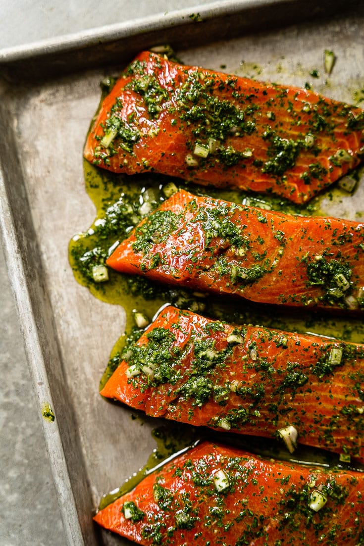 alaskan salmon filets on sheet pan marinating with chimichurri vertical