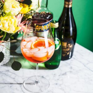 aperol spritz cocktail on white marble with bottles