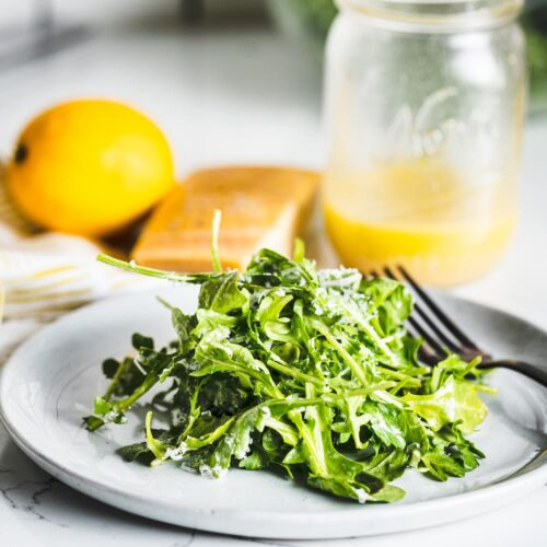 arugula salad with lemon vinaigrette on plate vertical