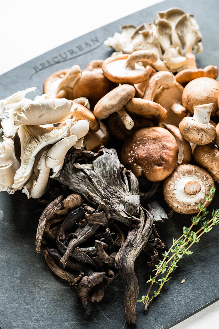 assorted wild mushrooms on cutting board