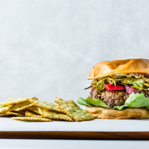 Brussels Sprouts and pickled beets burger on a brioche bun with chips
