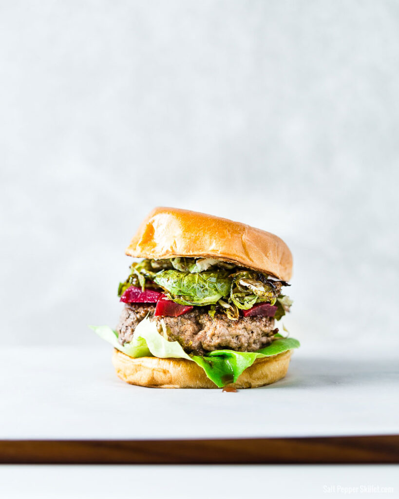 Brussels Sprouts and pickled beets burger on a brioche bun vertical