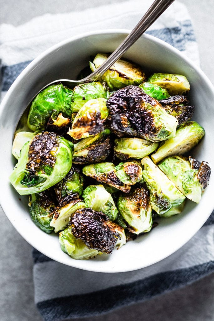 Crispy roasted brussels sprouts in bowl with serving spoon
