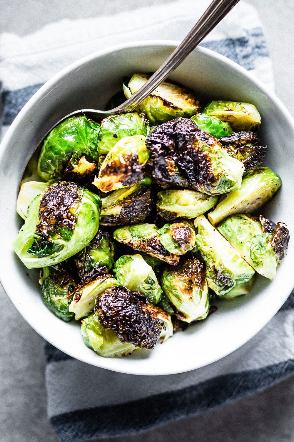 crispy brussels sprouts in bowl with serving spoon