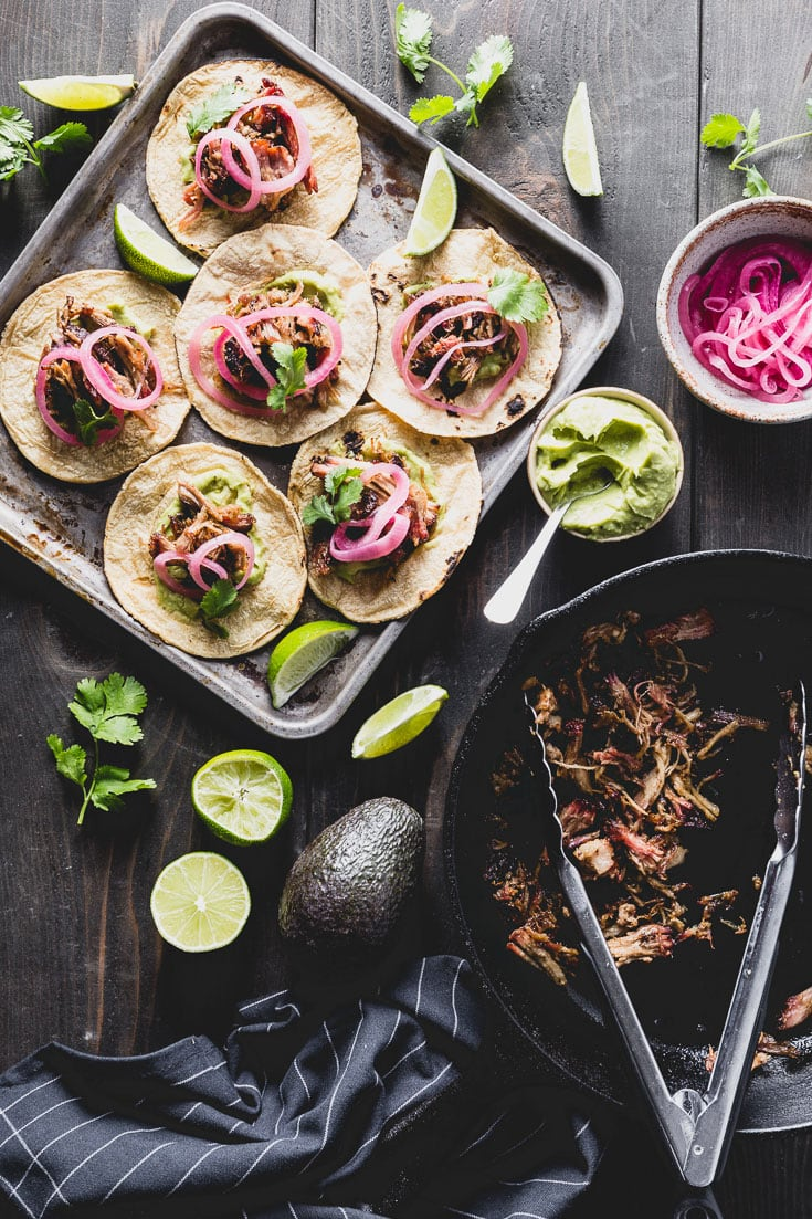 Crispy smoked pork carnitas tacos with avocado-lime crema, quick pickled onions and cilantro. Really, is there anything more perfect? #cincodemayo #carnitas #tacos #carnitastacos