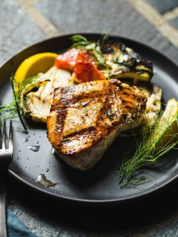 grilled swordfish on plate with lemon and fennel
