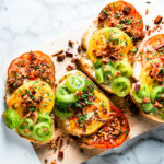 Heirloom Tomato Toast + bacon on cutting board horizontal