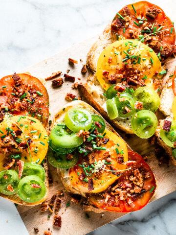Heirloom Tomato Toast + bacon on cutting board horizontal