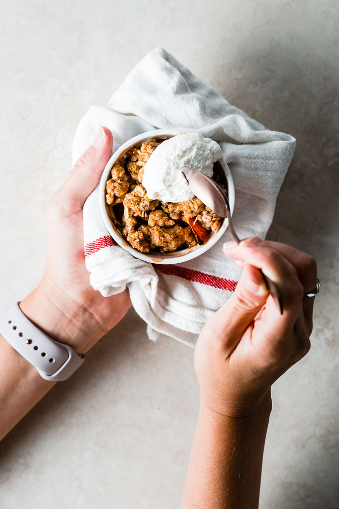 Individual Peach Crisps Recipe - One of the best ways to enjoy peaches is in individual peach crisps, where the natural sweetness of the peaches shines through and is complimented with a crunchy topping. #peaches #crisp #dessert #sweets #recipe SaltPepperSkillet.com