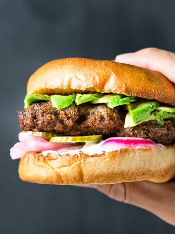 Holding Lamb Burger with Pickled Veggies and Yogurt-Mint Sauce horizontal