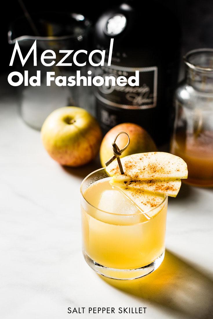 Smoky Apple Mezcal Old Fashioned Cocktail. A seasonal cool weather variation of the classic Old Fashioned cocktail with Mezcal, homemade apple syrup, orange bitters and garnished with an aromatic cinnamon dusted fanned apple. #cocktail #mezcal #oldfashioned