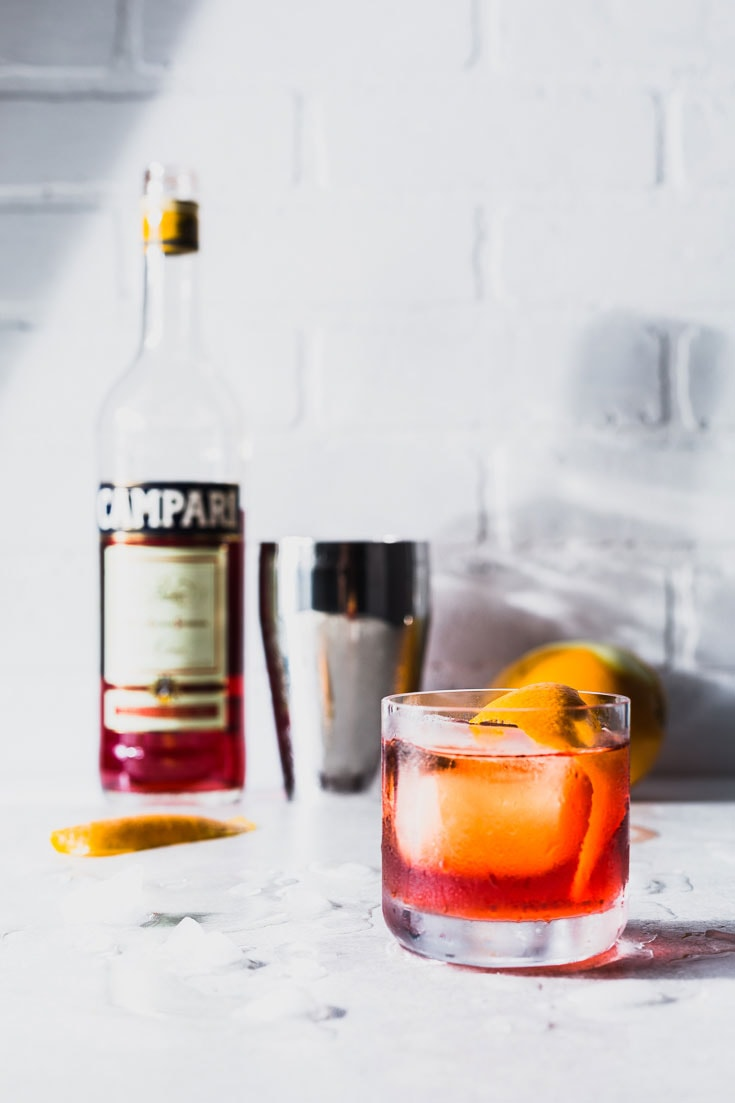negroni cocktail recipe vertical side with campari bottle