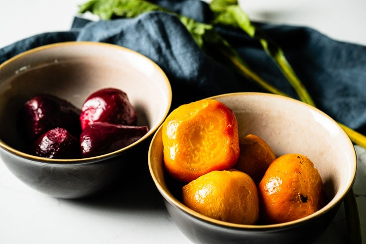 peeled and sliced roasted beets in bowls close up