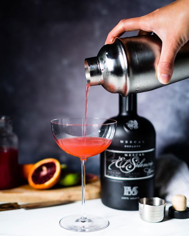pouring mezcal blood orange gimlet