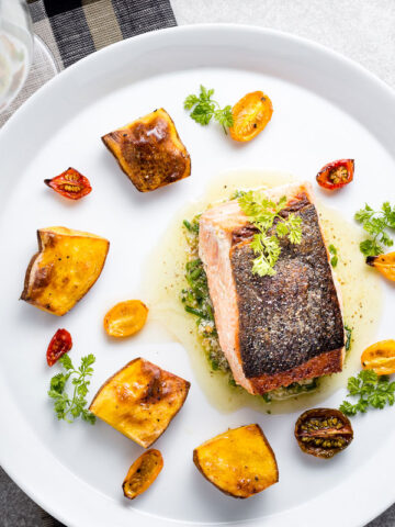 seared salmon with chive-walnut pistou, fingerling potatoes and half-dried tomatoes horizontal with wine