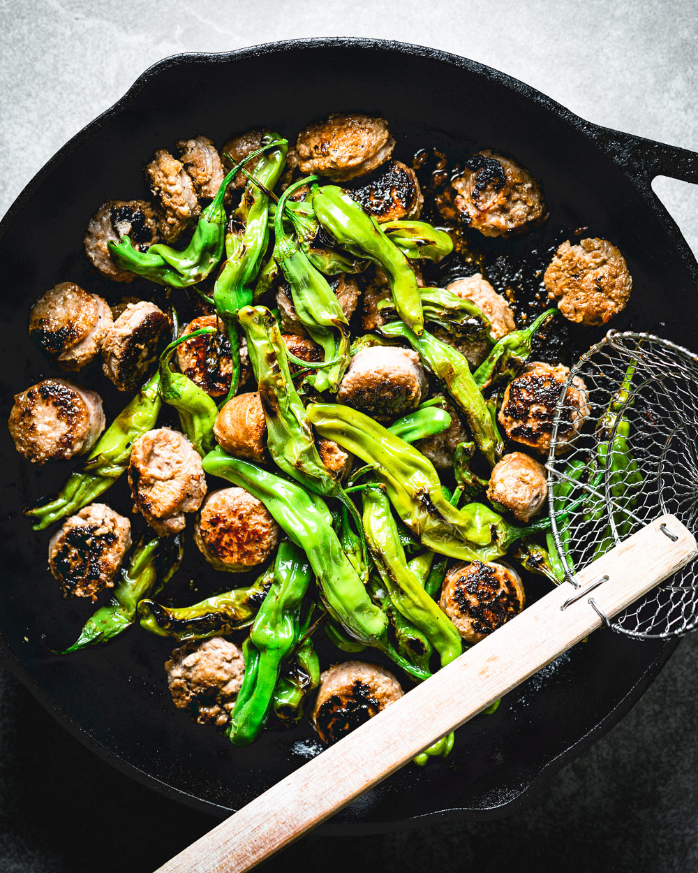 Shishito Peppers and Sausage in a cast iron skillet overhead