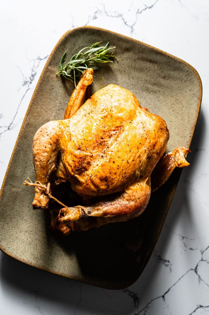 simple roast chicken on serving platter vertical