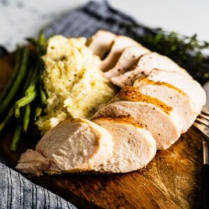 sous vide chicken breast sliced on wood plate horizontal